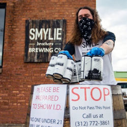 A brewer from Smylie outdoor, wearing a mask and gloves, dropping a beer order onto a to-go pickup station
