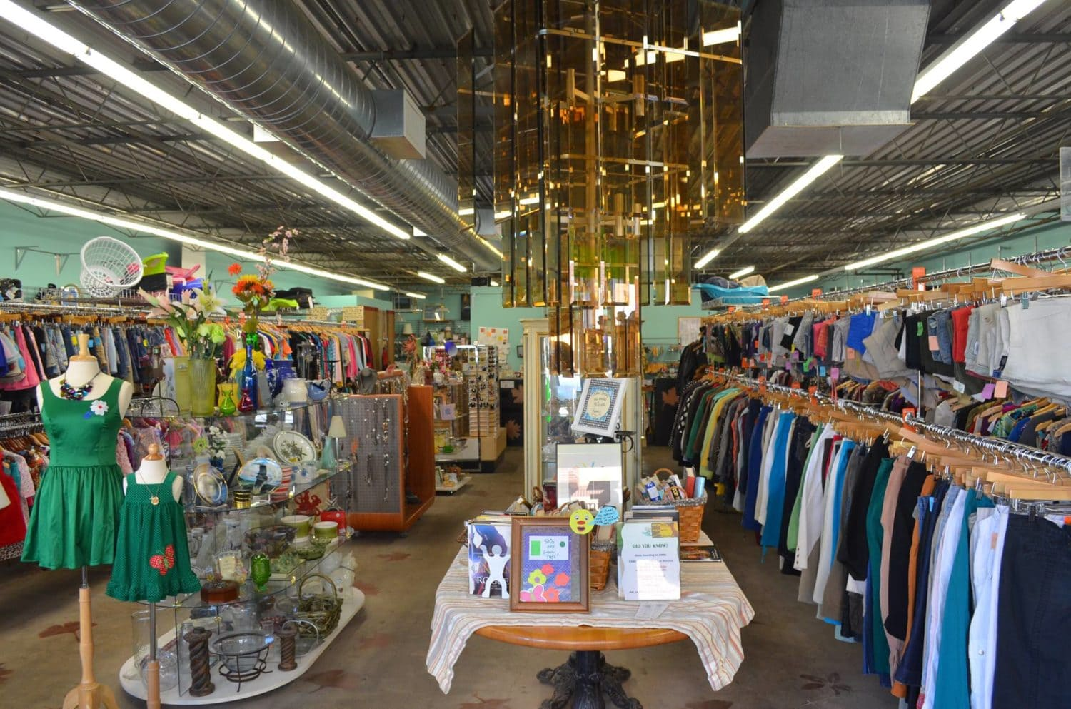 An interior photo of Family Tree Resale showing racks of clothing and tables with jewelry and home decor