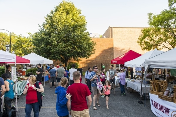 A crowd mingles outdoors between vendor tents at the Ravenswood Farmers Market