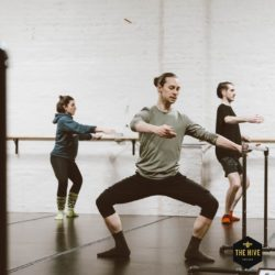 An instructor teaches youth students ballet in a chic industrial studio