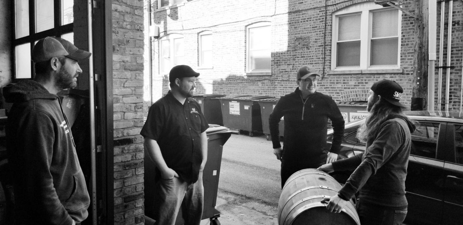 A picture of several Malt Row brewers reviewing a barrel being dropped off by KOVAL