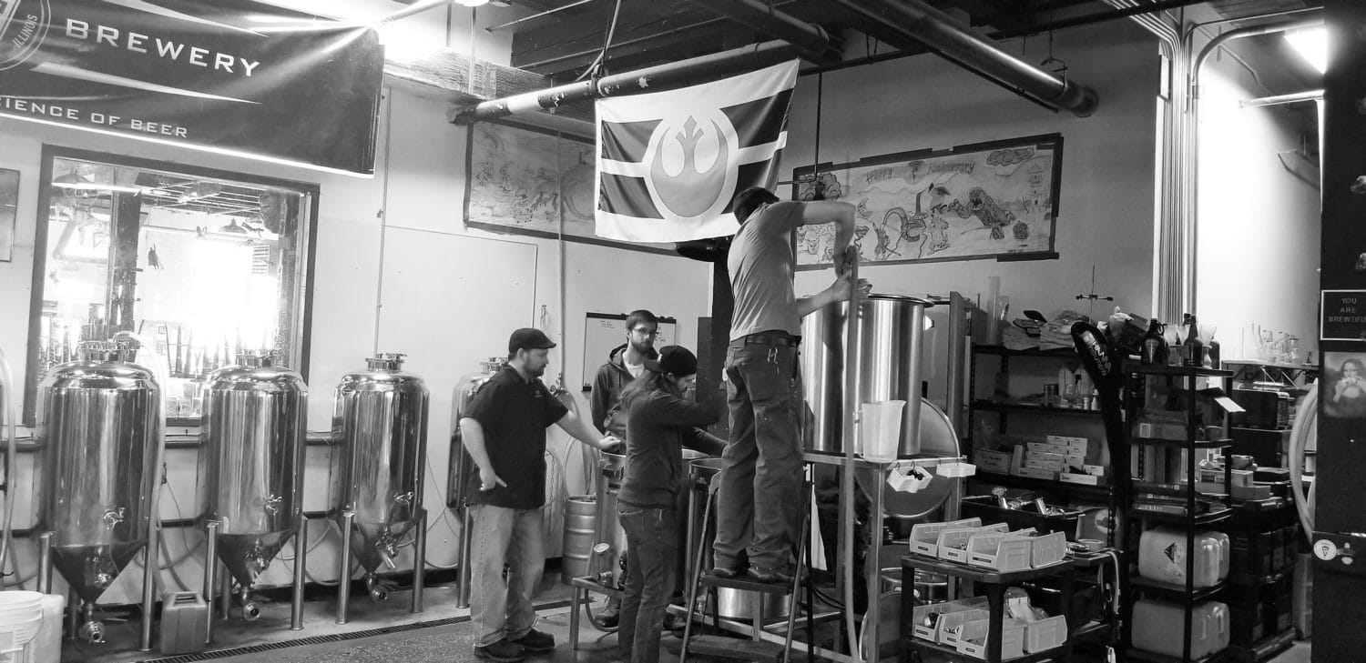 A picture of a group of brewers huddled over brewing equipment