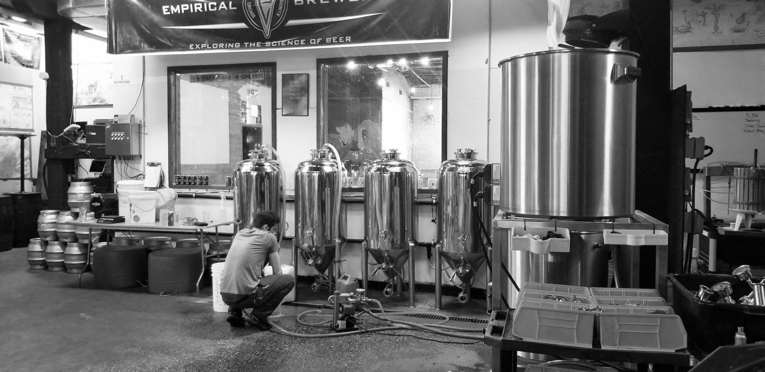 A picture of Empirical's Jacob Huston monitoring brewing equipment