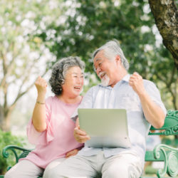 A senior adult couple on a park bench, celebrating while holding a tablet