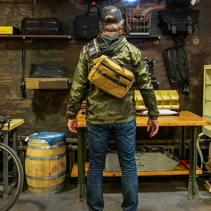 A man modeling the Insidious Jr sling bag made by DEFY