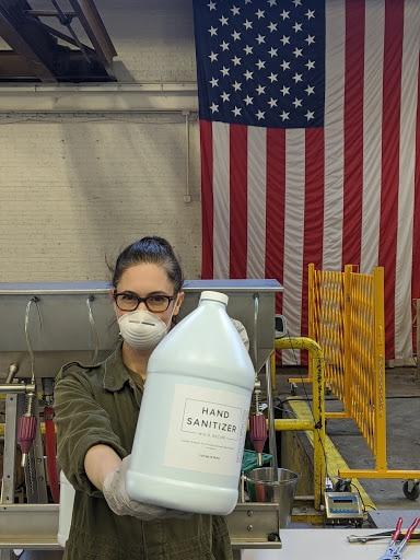 KOVAL owner Sonat Birnecker Hart showing off a gallon of KOVAL Sanitizer