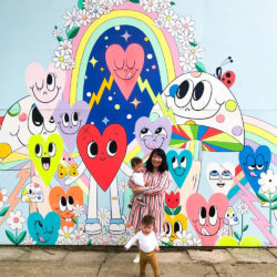 A mother poses with her children in front of Chris Uphues' Happy Garage mural along Ravenswood Ave