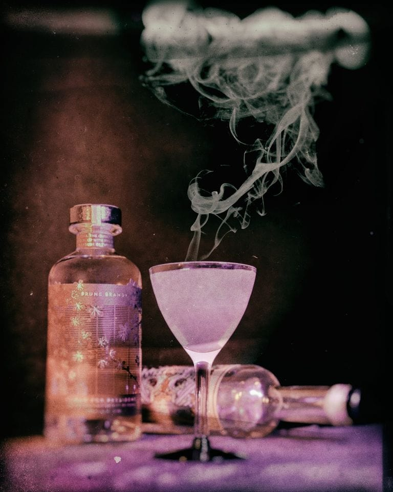 A cloudy KOVAL Halloween cocktail billowing smoke in front of a bottle of KOVAL gin